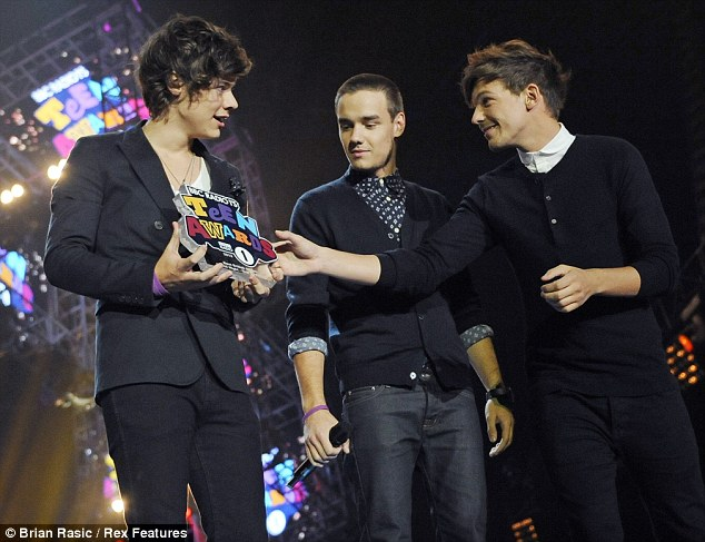 It's mine: Louis tries to steal the award from Harry, as a newly shaved Liam looks on