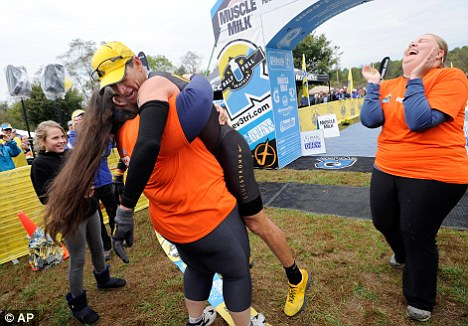 Helping hand: Cancer survivor Jessica Protasio picks up Lance Armstrong after he competed