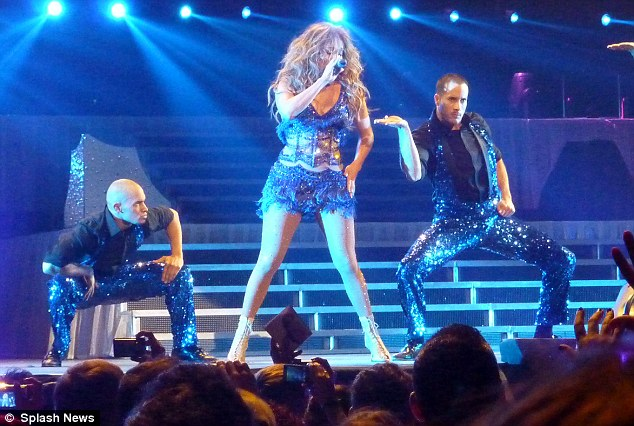 Highly-styled: The singer's back-up dancers matched her blue sequined ensemble with sparking pants of their own