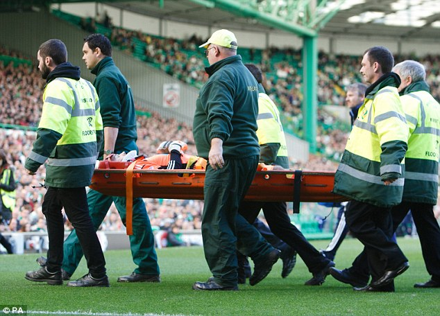 Injury blow: Hearts goalkeeper Jamie MacDonald is carried off after a collision with Celtic's Charlie Mulgrew