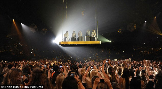 Stand out show: The One Direction singers hovered over the crowd's heads as they sat down to sing their tracks
