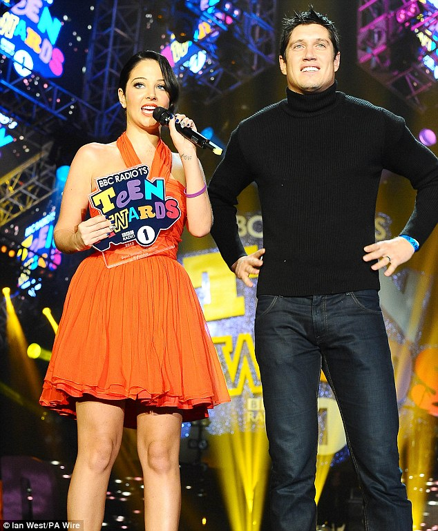 Star guest: Tulisa joined Radio 1 presenter Vernon Kay on stage as she stood out in her vibrant number while speaking into the mic