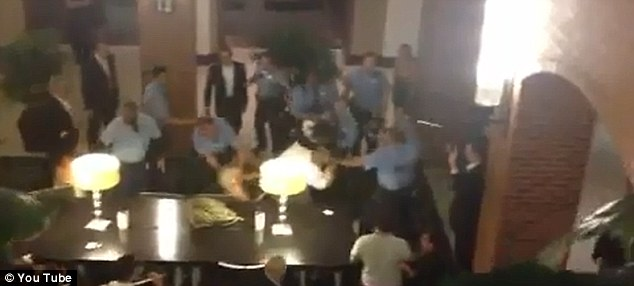Break it up: Officers can be seen using their batons to untangle two wrestling guests. Two people were cited and one was arrested