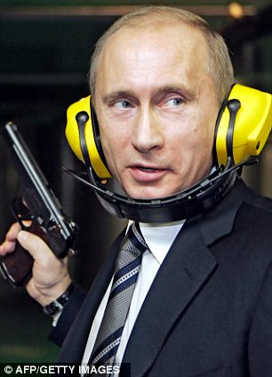 Russia's  President Vladimir Putin holding a pistol during his visit to a newly-built headquarters of the Russian General Staff's Main Intelligence Department (GRU) in Moscow.