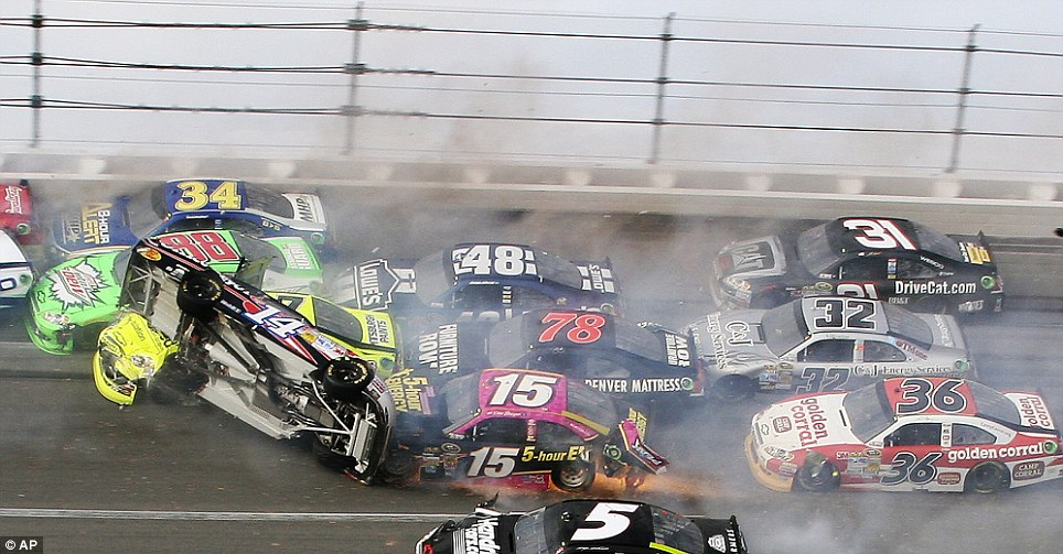 Back down to earth: As Stewart's car slid on its side, a 25-car pile-up was created