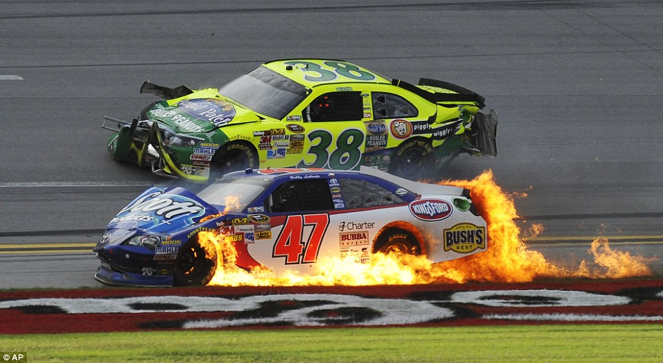 Balls of fire: Flames engulf Bobby Labonte's car as David Gilliland (No 38) passes after wrecking on the last lap
