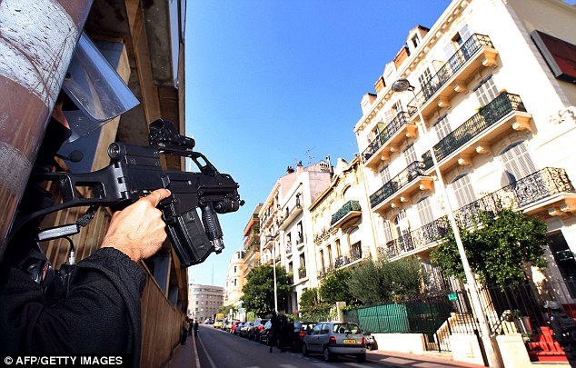 Under siege: Armed police on operation in Cannes, southeastern France, where Nsaku was arrested at his home in front of his shocked parents