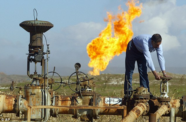 Iraqi oil to Syria: A worker turning a valve at the Shirawa oil field, where oil was first pumped in Iraq in 1927, outside the northern city of Kirkuk