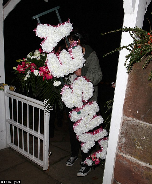 RIP: Production staff carry the wreath on to the set ready to film scenes for the funeral of Lynsey Nolan