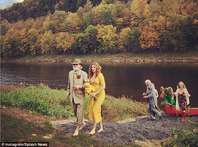 Beautiful barefoot: Amber donned a non-traditional canary yellow lace gown for her big day and was given away by her father Twin Peaks star Russ Tamblyn last Sunday in the woods of Upstate New York