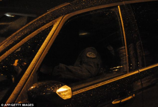 Done: A policeman is pictured leaving the scene in Torcy, east of Paris