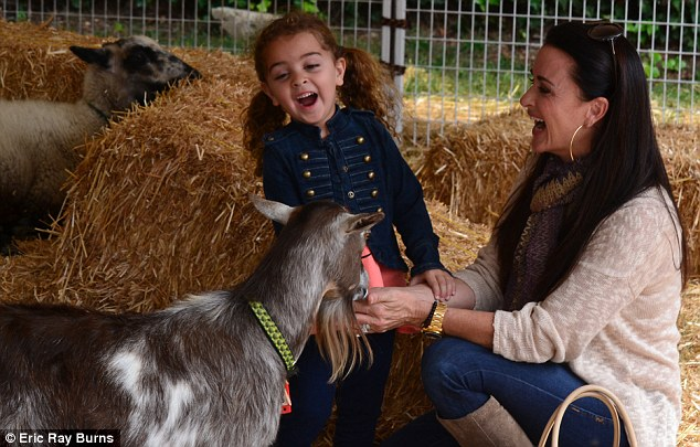 Having a laugh: The pair fed the goats and sheep