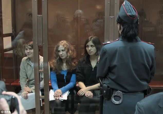 Appeal: The three members of punk-rock band Pussy Riot sit in a glass-walled cage in the court room before the beginning of the hearing at the Moscow City Court this morning