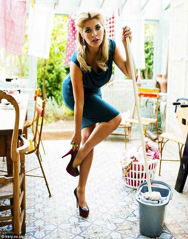 Careful you don't slip in those heels! Holly Willoughby mops the floor... while wearing vertiginous heels as she models her new Very.co.uk collection