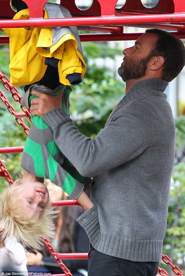 Monkeying around: At the playground at the park, Samuel had a ball with doting father Liev lifting him up on the monkey bars