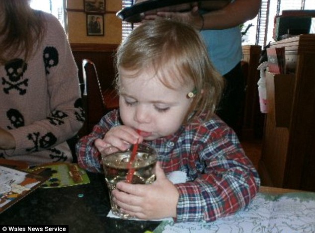 Mix-up: A family photo of Sonny Rees, two, tucking into a whisky and water in the Swansea branch of Frankie & Benny's on Saturday. The image was taken when his parents thought he was drinking lime and water