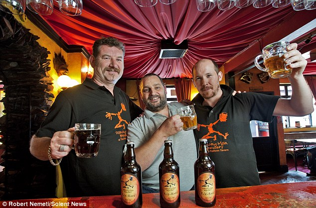Merry fellow: (left/right) Stewart Cross, Rob Brown and Aidan Lavin enjoy a quick pint of the beer in the Platform Tavern, in Southampton where the beer is produced