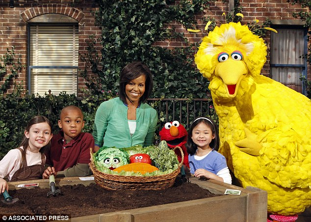 Caught in the middle: Big Bird, seen here with Michelle Obama on Sesame Street, has been thrust into the battle for the presidency after Romney said he would cut funding to the broadcaster which airs the show