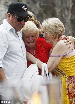 A relative of one of the victims is comforted as she breaks down in tears