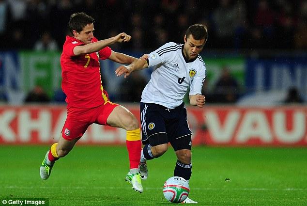 Come here! Premier League stars Joe Allen (left) and Shaun Maloney (right) battle for possession