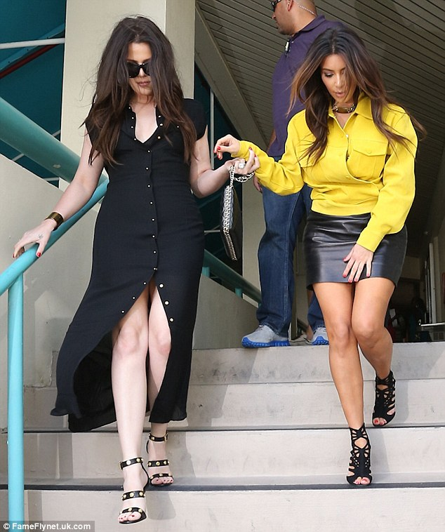 Helping hand: Khloe helped Kim down the stairs, as Kanye's girl tried desperately not to flash the photographers in her very short skirt
