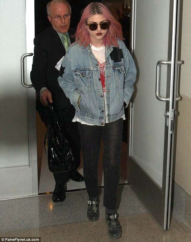 Used up the bleach? Frances Bean Cobain wore pink hair as she marched through Los Angeles International Airport on Friday