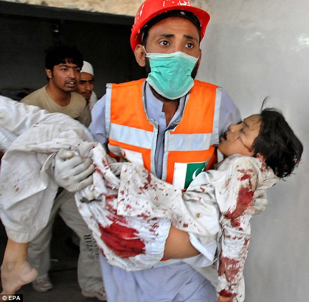 Tragic: A paramedic with a wounded child at a local hospital in Peshawar, Pakistan
