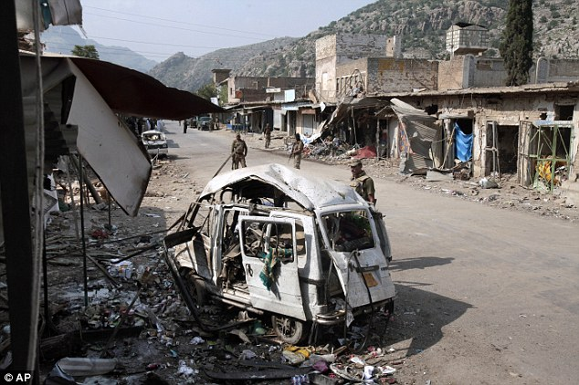 Havoc: Pakistani Army soldiers stand at the site of a car bomb explosion that killed 17 people in the Pakistani town of Darra Adam Khel in the troubled Khyber Pakhtunkhwa province bordering Afghanistan