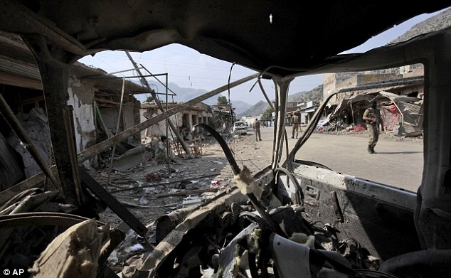Wreckage: Seen through the wreckage of a vehicle, Pakistani Army soldiers check the site where a powerful car bomb went off outside the offices of pro-government tribal elders in northwestern Pakistan