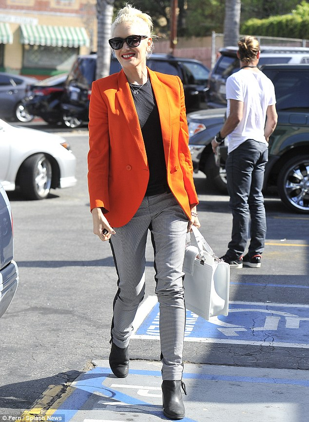 Feeling seasonal: Gwen Stefani donned a pumpkin orange jacket as she took her sons Zuma and Kingston to a Halloween party today