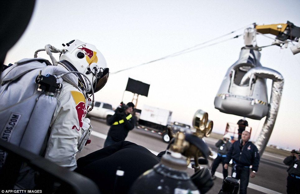 Time to go to work: Baumgartner is pictured on Sunday stepping out of a trailer in preparation for his ascent into the edge of space