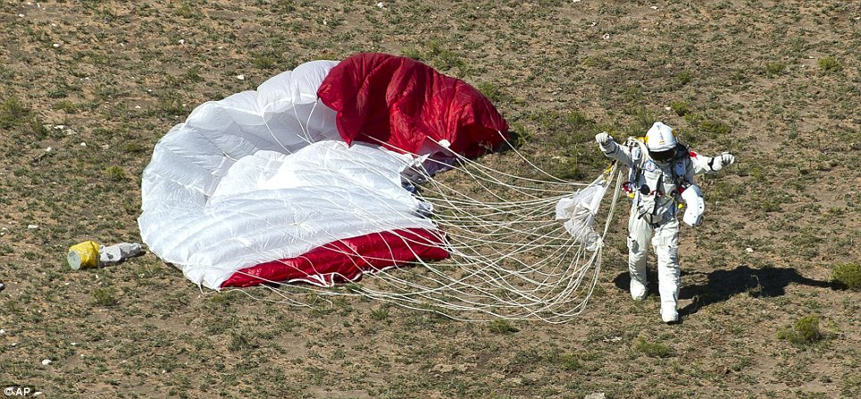 Grounded: Baumgartner raises his hands in the air after a safe landing from 24 and a half miles above the earth