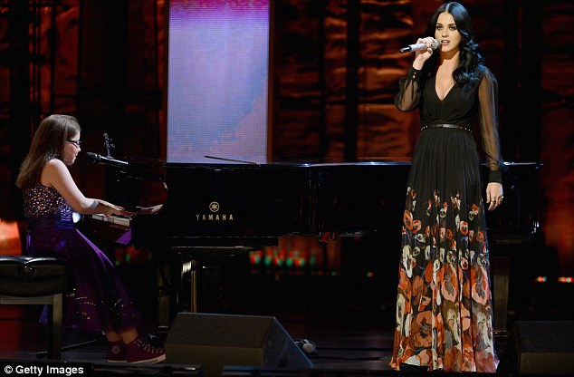 Special performance: Katy sings for the audience, accompanied by a young girl on piano