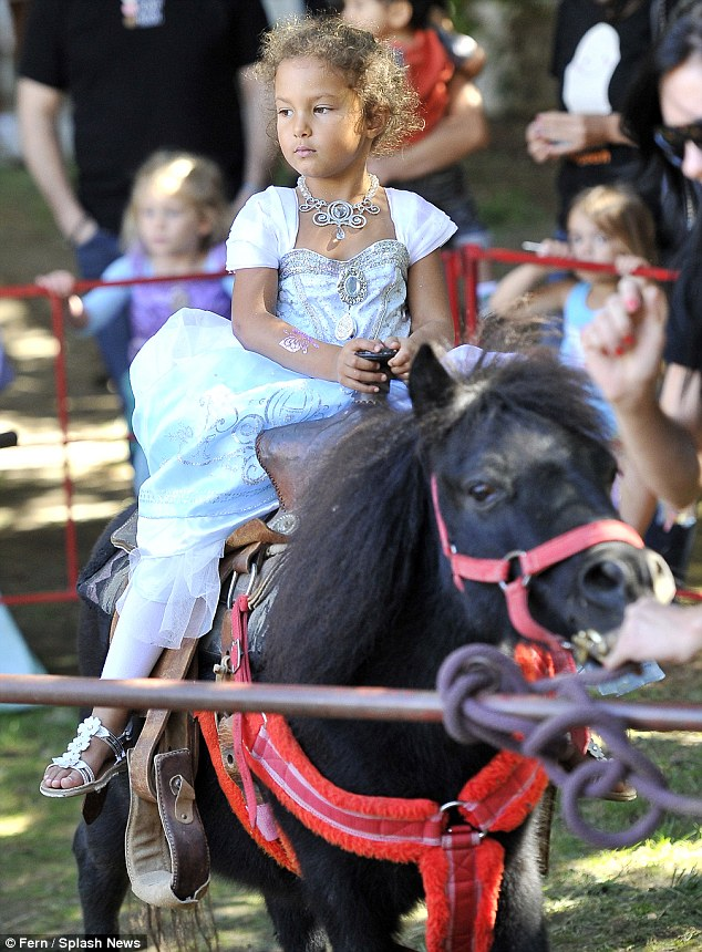 Little princess: The six-foot-two stud dutifully watched on as Nahla - wearing a white ball gown and ornate necklace - rode atop a black Shetland pony