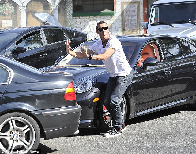 Hold it! Gavin plays valet guy as he stops a car backing up into his wife's Porsche