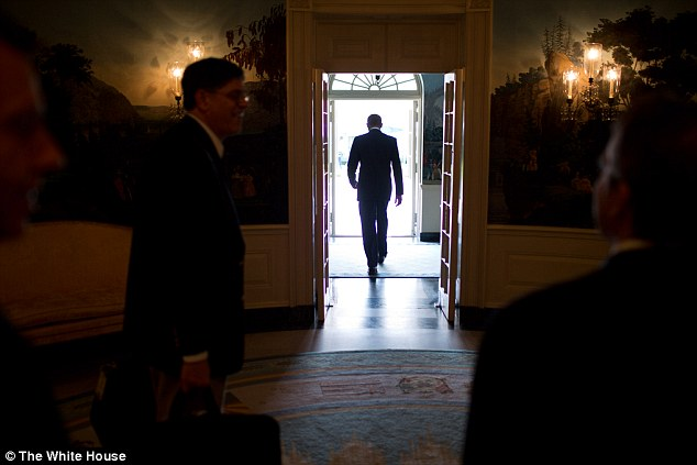 Silhouette: President Barack Obama, centre, departs the Diplomatic Reception Room of the White House to board Marine One on the South Lawn, on September 30