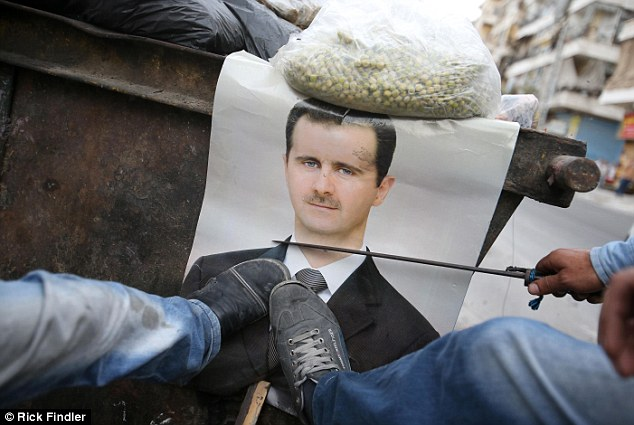 Battle goes on: A picture of Syrian President Bashar Assad is kicked and defaced by members of the Free Syrian Army as the troubles show no sign of letting up