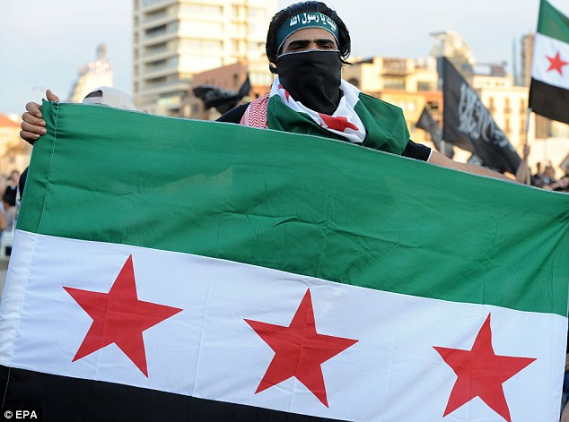 Opposition: An anti-Syrian regime protester holds and covers his face with the Syrian pre-Baath flag during a protest against the Syrian regime at Martyrs Square in Beirut, Lebanon