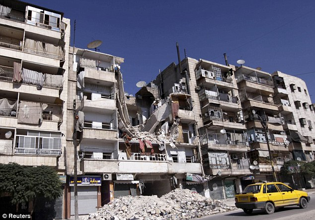 Carnage: A taxi drives past a damaged building in the al Katerji Tariq district in Aleppo city in northern Syria