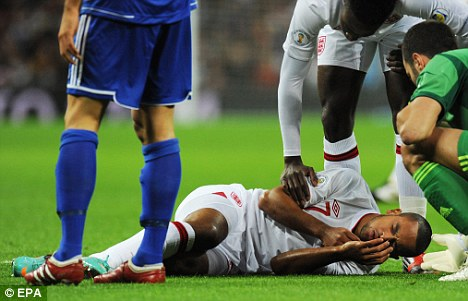Crocked: Theo Walcott is set to be replaced by James Milner on the right