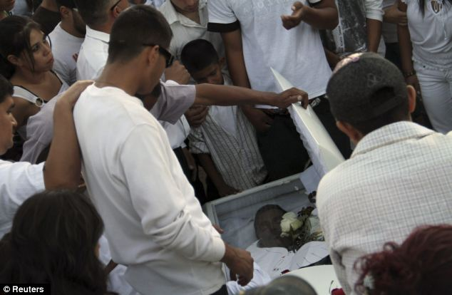 Relatives and friends look at the body of Jose Antonio Elena Rodriguez in a coffin during his funeral on Sunday