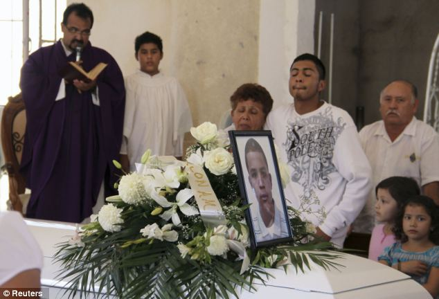 Relatives cry beside a coffin containing Jose Antonio Elena Rodriguez who was found dead at the border from gunshot wounds about midnight last Wednesday