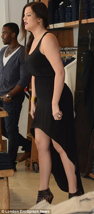 Sophisticated: Khloe sported a slick of crimson lipstick, and smoky eye make-up in the store