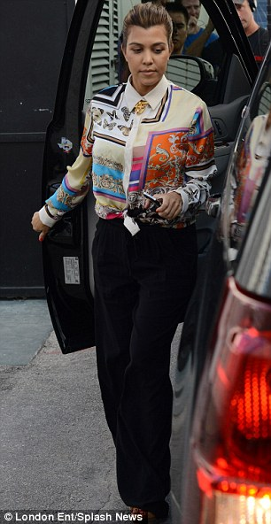 More conservative: Kourtney Kardashian looked more conservative in a brightly patterned short and black trousers as she arrived at the store