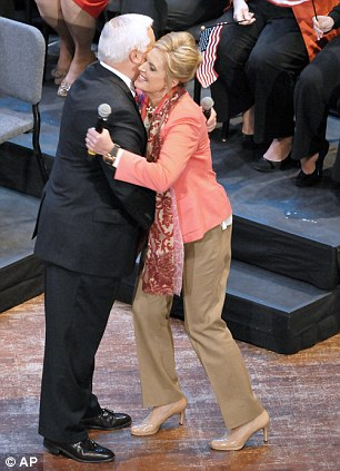 Into battle: Ann Romney is greeted by Governor Tom Corbett on Monday as Michelle Obama rallies the Ohio gathering