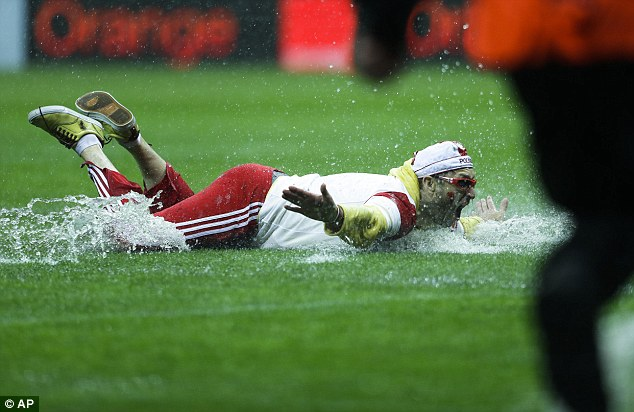 Splish splash: One Poland fans makes the most of the inclement weather