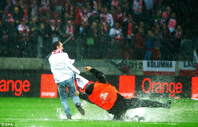 Soak it up: One steward takes a tumble trying to stop a pitch invader as fans watch on