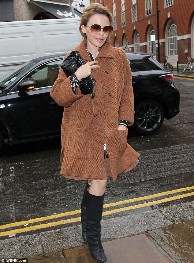 Stylish: The diminutive pop princess looked effortlessly chic in a zip-through cardigan, which she teamed with black leather boots and her obligatory sunglasses
