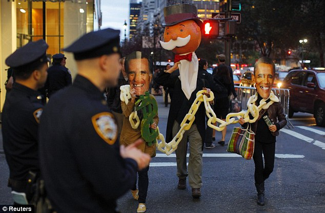 Public opinion: Protesters wear Obama and Romney masks as they take part in rally in support of Medicaid funding, outside the Waldorf Astoria hotel in New York