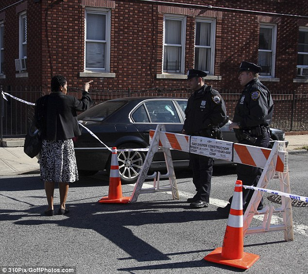 Shaken: A pedestrian talks with police officers blocking the street where Smith was murdered